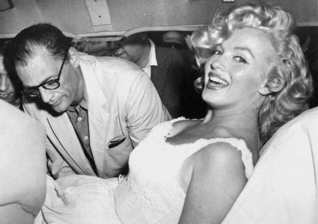 Marilyn Monroe is made comfortable in a car by her husband, playwright Arthur Miller, following her release from Doctors Hospital, New York City, August 10, 1957.