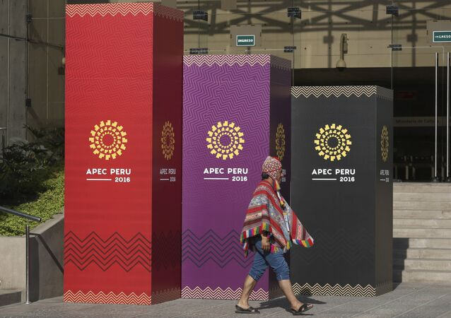 A man dressed in traditional Andean clothes walks past the logo of the APEC 2016 summit in Lima, Peru, Wednesday, Nov. 16, 2016