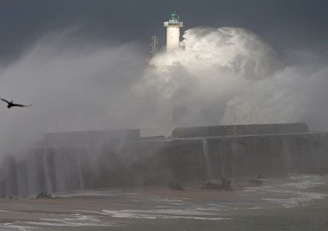 Waves crash against a lighthouse as the wind blows at around 120 kph (75mph), in Boulogne-sur-Mer, northern France