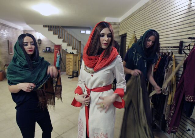 Female Iranian models Golenaz, center, Sepideh, left, and Sherila Hosseinkhani, wear dresses designed by female designer Sanaz, in a model photography session, in Tehran, Iran. (File)