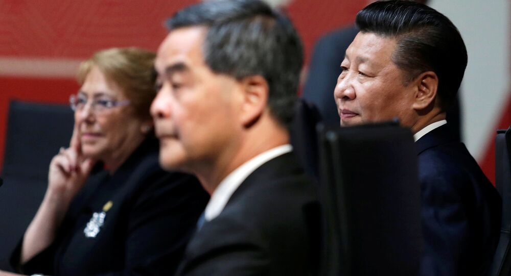Chile's President Michelle Bachelet (L), China's President Xi Jinping (R) and Hong Kong Chief Executive Leung Chun-ying sit together during the APEC (Asia-Pacific Economic Cooperation) Summit in Lima, Peru