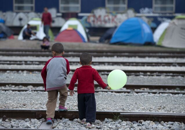 Children cross rail tracks at a makeshift camp for migrants and refugees near the village of Idomeni not far from the Greek-Macedonian border