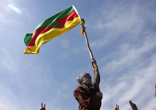 A masked Kurdish man waves a PKK's flag