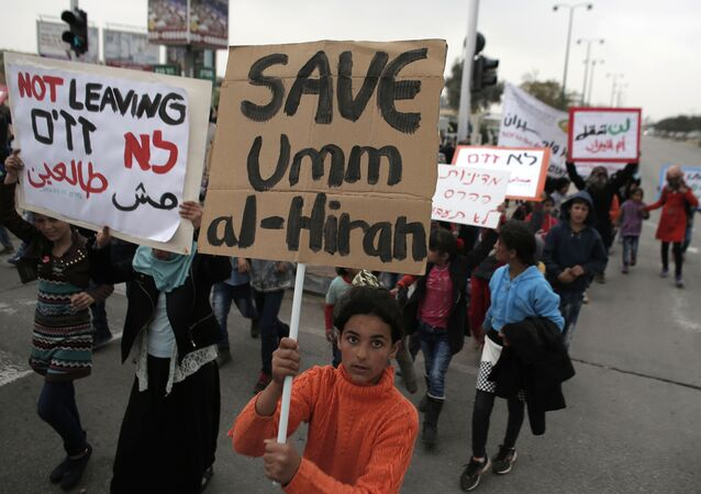 Bedouins hold placards during a protest against a plan to uproot the Umm Al-Hiran village, which is not recognized by the Israeli government, in the southern Israeli city of Beersheva in the Negev desert (File)