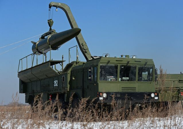 A transporter-loader places an Iskander-M shorter-range missile onto a self-propelled launcher during an exercise involving missile and artillery units of the Eastern Military District's Fifth Russian Army in the Primorye Territory