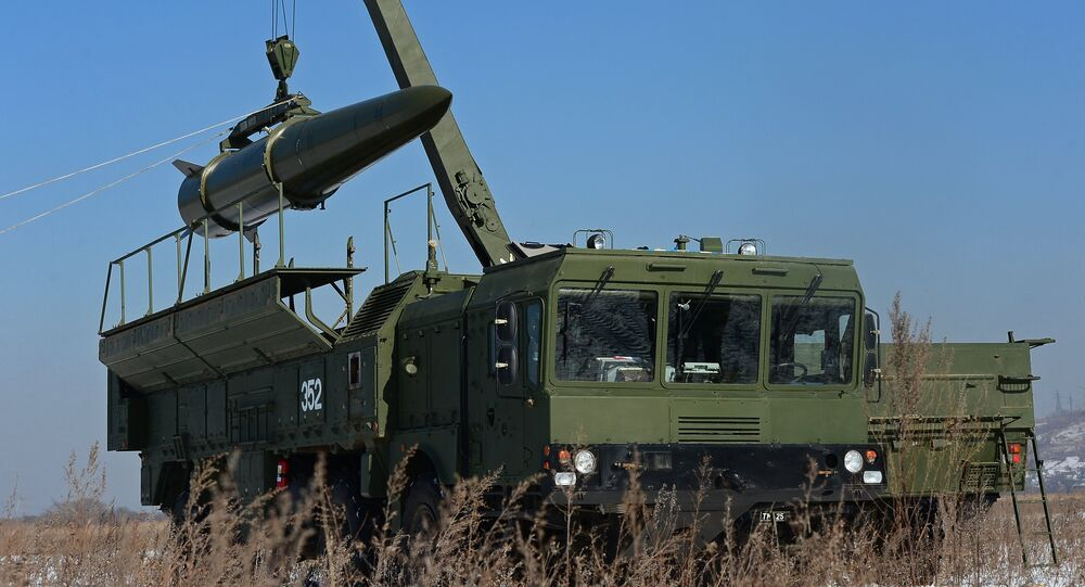 A transporter-loader places an Iskander-M shorter-range missile onto a self-propelled launcher