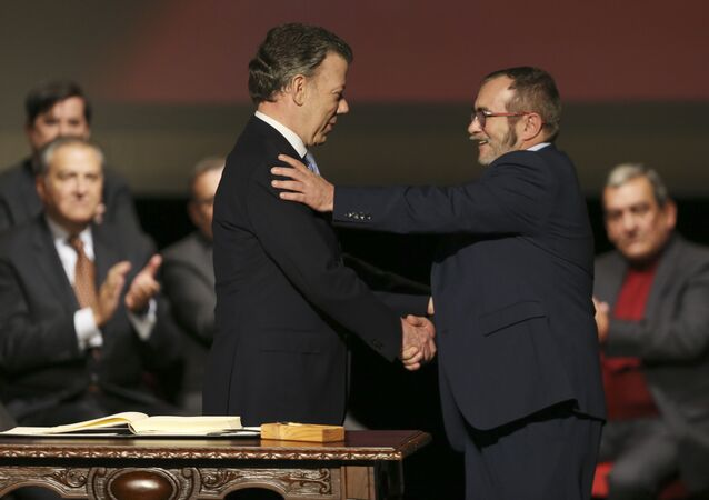 Colombia's President Juan Manuel Santos, left, shakes hands with with Rodrigo Londono, known as Timochenko, the top leader of the Revolutionary Armed Forces of Colombia, FARC, after signing a revised peace pact at Colon Theater in Bogota, Colombia, Thursday, Nov. 24, 2016