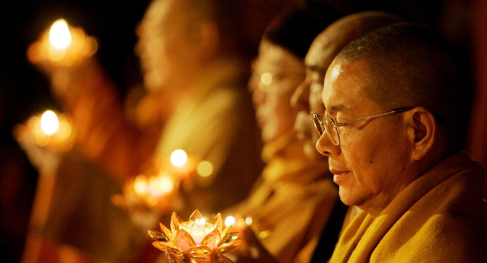 Buddhist monks hold candles during Transmission of Lamp as part of the World Buddhist Forum at Puji Monastery Saturday April 15, 2006 in Mount Putuo, China