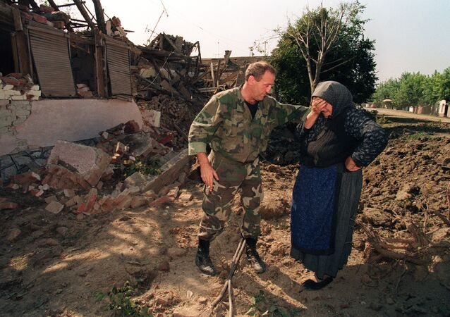 A Croatian National Guardsman comforts an old woman on September 26, 1991, outside her home which was destroyed in an air raid during the night by Yugoslav Serbian Federal air forces