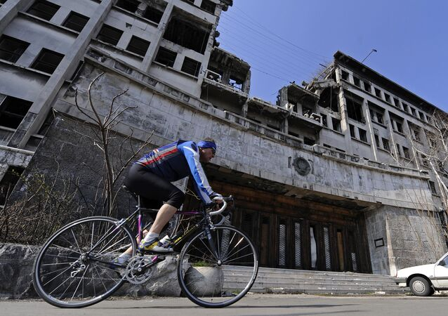 A man rides his bike on March 22, 2009 past the building of the former federal Interior Ministry in Belgrade, which was destroyed during the 1999 NATO air campaign against Serbia and Montenegro
