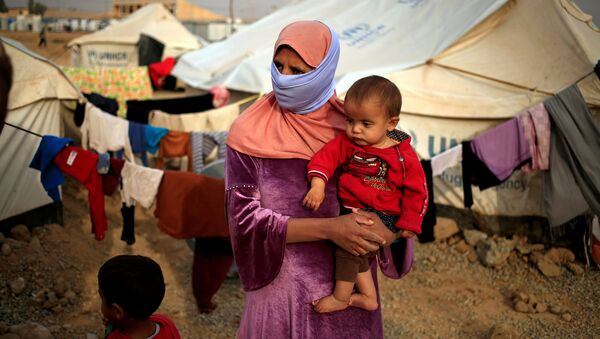 A woman who fled from Mosul carries her five-month-old daughter Ritadj, who was born under Islamic State rule and has no identity documents recognised by Iraqi authorities, in Debaga refugee camp, Iraq November 10, 2016 - Sputnik International