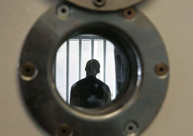 A security guard is seen through a small security window, in a room in the long-term wing at the new Colnbrook Immigration Removal Centre near London's Heathrow Airport, Thursday Sept. 16, 2004