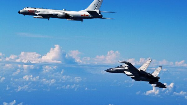 Chinese People's Liberation Army Air Force Su-30 fighter, right, flies along with a H-6K bomber as they take part in a drill near the East China Sea (File) - Sputnik International