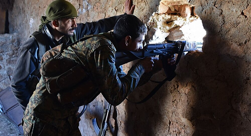 A fighter from the Syrian pro-government forces mans a riffle inside a damaged house in the recently recaptured village of Joubah during an offensive towards the area of Al-Bab in Aleppo province, on November 25, 2016