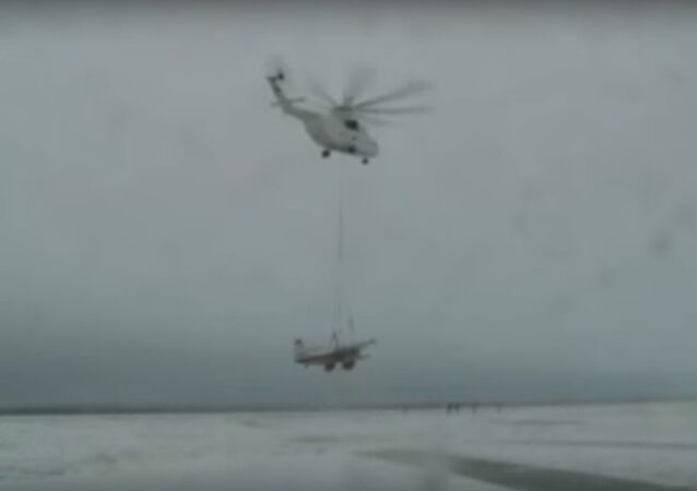Mi-26T helicopter airlifts a plane
