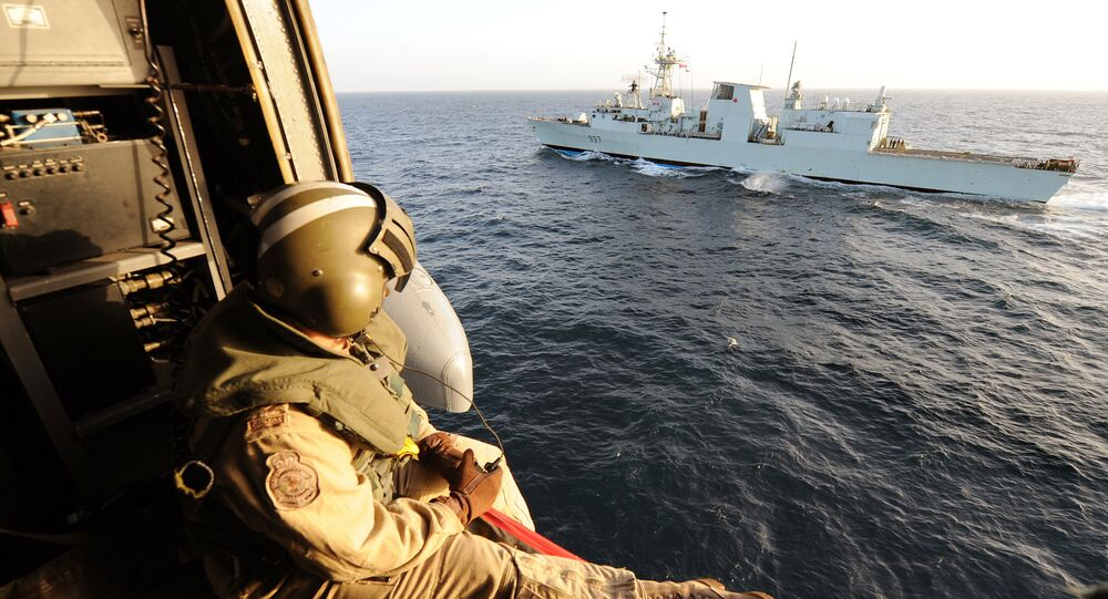 Canadian helicopter Sea-King of the military ship Fredericton flies near Canadian military boat during a flying security patrol on January 9, 2010 in the Aden Gulf