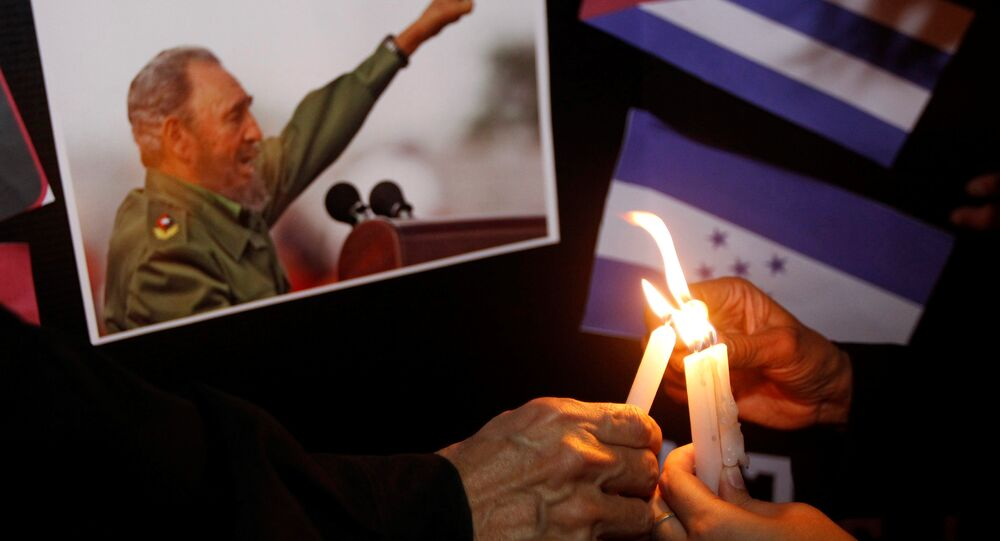 People place candles beside a picture of Fidel, as part of a tribute, following the announcement of the death of Cuban revolutionary leader Fidel Castro, in Tegucigalpa, Honduras November 26, 2016