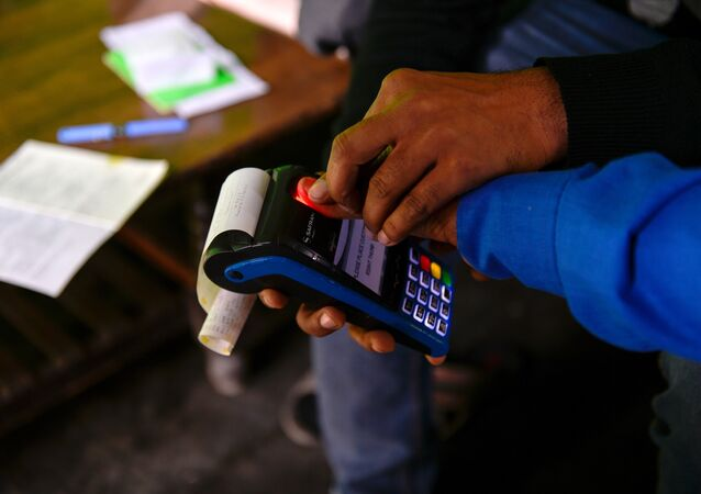 In this photograph taken on November 16, 2016, bank correspondent Mohammad Imran helps a villager to take his thumb print on a mobile banking machine in Basendua village in Bulandshahr, in northern Uttar Pradesh state