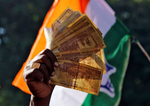 A man displays 500 Indian rupee notes during a rally organised by India's main opposition Congress party against the government's decision to withdraw 500 and 1000 Indian rupee banknotes from circulation, in Ajmer, India, November 24, 2016.