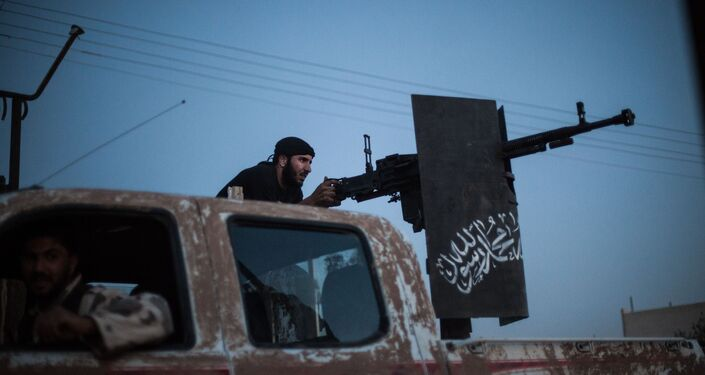 A member of Ahrar al-Sham fires against a position of the Committees for the Protection of the Kurdish People (YPG) during clashes in the countryside of the northern Syrian Raqqa province on August 25, 2013.