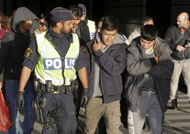 A group of migrants off an incoming train walk down a platform as they are accompanied by the police at the Swedish end of the bridge between Sweden and Denmark near Malmo