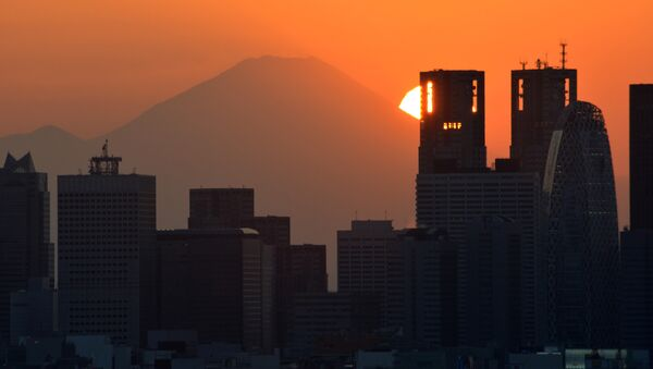 This picture taken on November 7, 2016 shows the sun setting behind the Japan's highest mountain Mount Fuji and skyscrapers in Tokyo's Shinjuku area. - Sputnik International