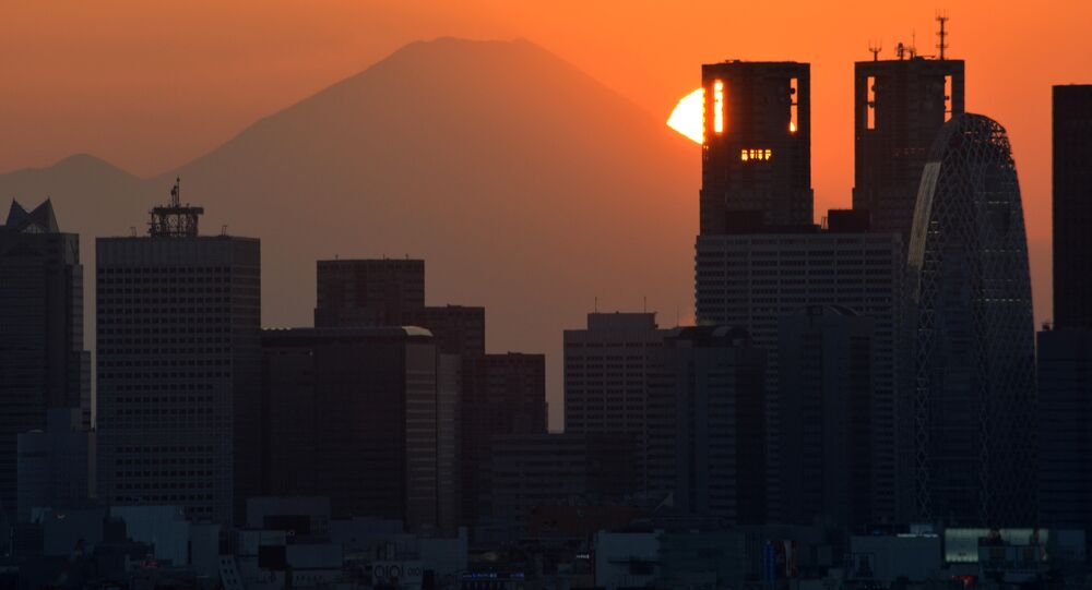 This picture taken on November 7, 2016 shows the sun setting behind the Japan's highest mountain Mount Fuji and skyscrapers in Tokyo's Shinjuku area.