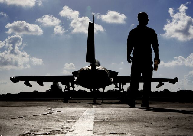 This photo taken on September 22, 2016 shows a British soldier walking by a Eurofighter Typhoon fighter jet at Royal Air Force's Akrotiri base in Cyprus, before taking off for a coalition mission over Iraq.