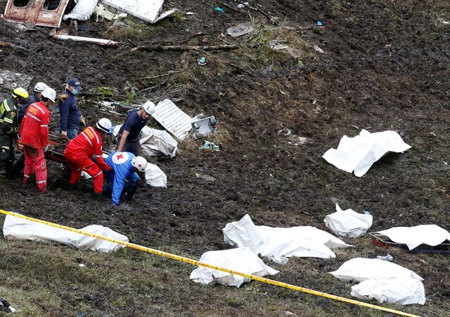 Rescue workers carry the body of a victim from a plane that crashed into Colombian jungle with Brazilian soccer team Chapecoense, near Medellin, Colombia