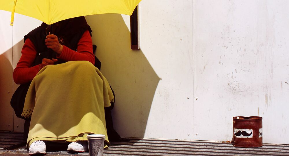 A beggar shields herself from the sun using a bright yellow umbrella, Malmo, Sweden