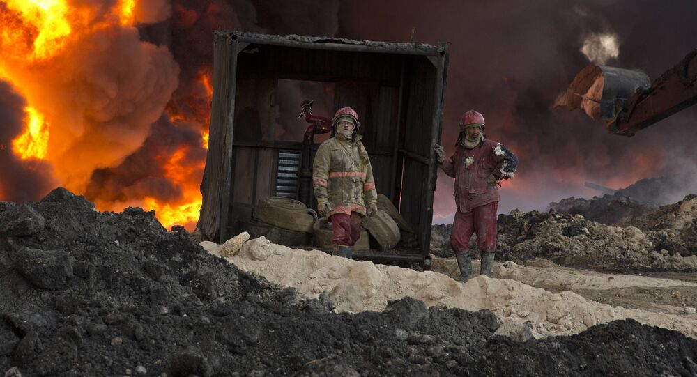 Fire fighters work to quell an oil fire set by Islamic State militants in Qayara, south of Mosul, Iraq, Monday, Nov. 28, 2016.