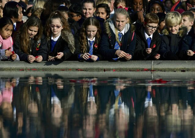 School children throw poppies into a fountain during an Armistice Day event at Trafalgar Square in London, Britain November 11, 2016.