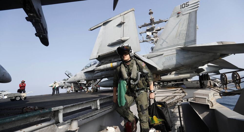 In this Tuesday, Nov. 22, 2016 photo, Lt. Jennifer Sandifer, a 27-year old fighter pilot from Austin, Texas, walks towards F/A-18E Super Hornet jet before launching from the deck of the U.S.S. Dwight D. Eisenhower aircraft carrier towards targets in Iraq and Syria