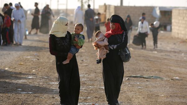 Iraqi refugees, who fled due to the ongoing conflict between pro-government forces and Islamic State (IS) group jihadists, walk at a camp in the northeastern town of al-Hol in Syria's Hasakeh province on October 19, 2016 - Sputnik International