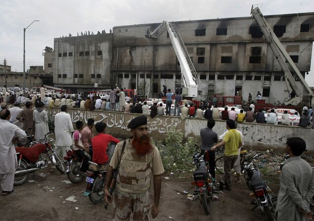 People gather at the site of burnt garment factory in Karachi, Pakistan on Wednesday, Sept. 12, 2012