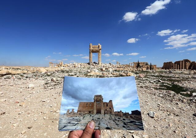 A general view taken on March 31, 2016 shows a photographer holding his picture of the Temple of Bel taken on March 14, 2014 in front of the remains of the historic temple after it was destroyed by Islamic State (IS) group jihadists in September 2015 in the ancient Syrian city of Palmyra