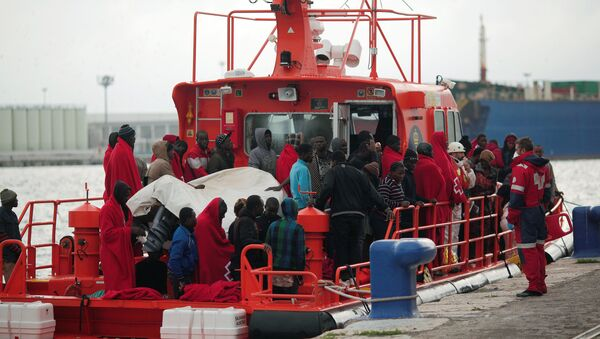 Migrants, who were part of a group intercepted aboard a dinghy off the coast in the Mediterranean sea, stand on a rescue boat upon arriving at a port in Malaga, southern Spain, December 3, 2016 - Sputnik International
