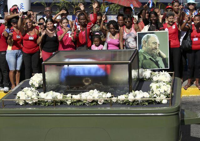 Residents wave as the caravan carrying the ashes of Cuba's late President Fidel Castro arrives in Santiago de Cuba, Cuba, December 3, 2016
