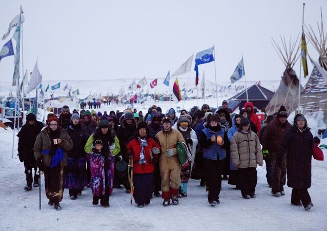 In this Thursday, Dec. 1, 2016 photo, Beatrice Menase Kwe Jackson, center, walks with Daniel Emory, both of the Ojibwe Native American tribe as they lead a procession to the Cannonball river for a traditional water ceremony at the Oceti Sakowin camp where people have gathered to protest the Dakota Access oil pipeline in Cannon Ball, N.D.