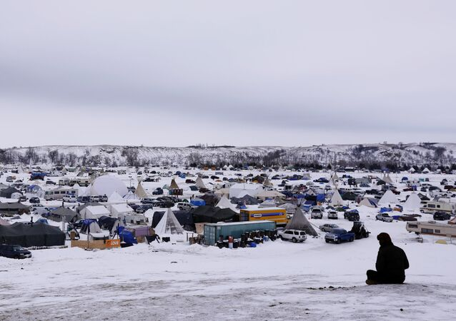 A man rests on top of a hill inside of the Oceti Sakowin camp as water protectors continue to demonstrate against plans to pass the Dakota Access pipeline near the Standing Rock Indian Reservation, near Cannon Ball, North Dakota, U.S., December 2, 2016