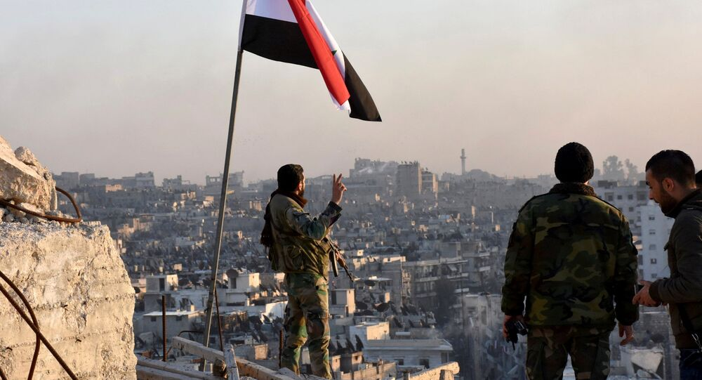 A Syrian government soldier gestures a v-sign under the Syrian national flag near a general view of eastern Aleppo after they took control of al-Sakhour neigbourhood in Aleppo, Syria in this handout picture provided by SANA on November 28, 2016