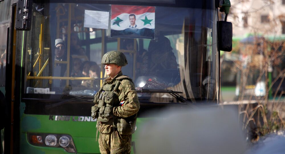 A Russian soldier stands near a bus carrying people who came back to inspect their homes in government controlled Hanono housing district in Aleppo, Syria December 4, 2016