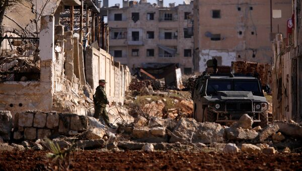 A Russian soldier walks to a military vehicle in goverment controlled Hanono housing district in Aleppo, Syria December 4, 2016 - Sputnik International