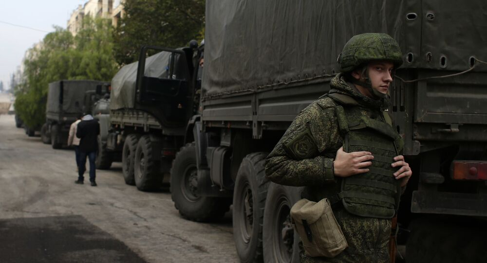 A Russian soldier stands next to an aid convoy in Aleppo, Syria, Sunday, Dec. 4, 2016