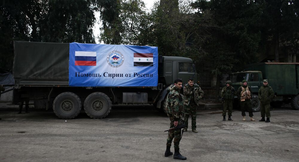 Russian and Syrian soldiers stand next to an aid convoy in Aleppo, Syria, Sunday, Dec. 4, 2016