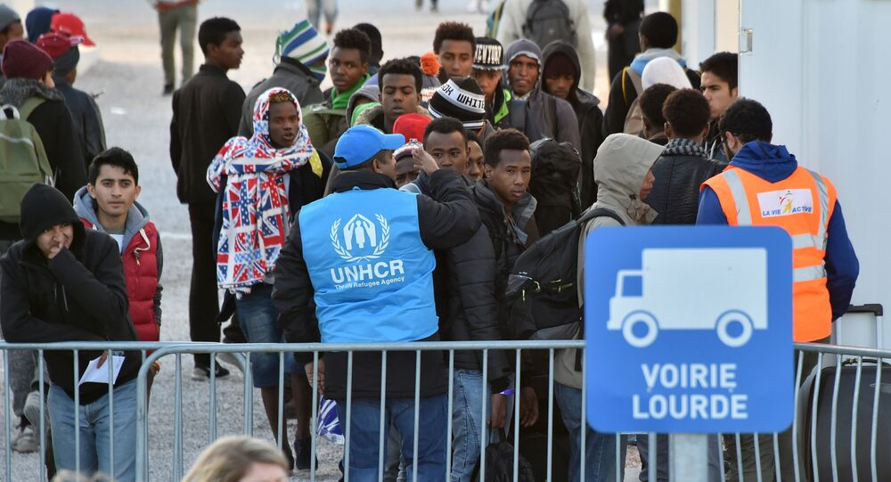 Volonteers of the United Nations High Commissioner for Refugees (UNHCR) agency and La Vie Active association help unaccompanied migrant minors, from the demolished Jungle migrant camp in Calais, to board a bus to travel to reception centres around France on November 2, 2016 in Calais, northern France