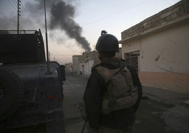 An Iraqi special forces soldier, stands next to a Humvee, as he looks at black smoke rising during a battle against the Islamic State militants, in the Bakr front line neighborhood, in Mosul, Iraq, Saturday, Nov. 26, 2016