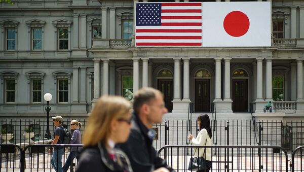 Pedestrians pass infront of US and Japan flags on the Eisenhower Executive Office Building next to the White House on April 27, 2015 in Washington, DC - Sputnik International