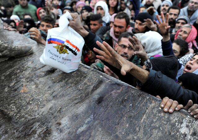 Syrians who have been evacuated from eastern Aleppo, reach out for Russian food aid in government-controlled Jibreen area in Aleppo, Syria November 30, 2016. The text on the bag, which shows the Syrian and Russian national flags, reads in Arabic: Russia is with you.
