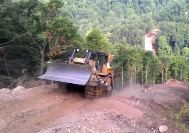 Extreme descent from the mountain on a bulldozer